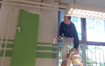 Maler, auf einer Leiter, streicht eine Wand
