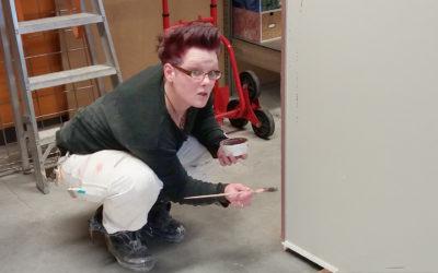 Eine Malerin streicht die Ecke einer Wand