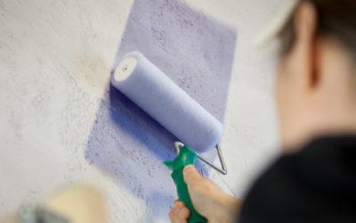 Eine Person mit einer Farbrolle malt eine Wand lila.