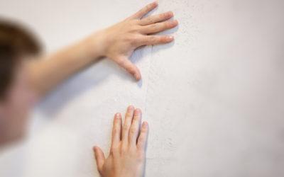 Hände tapezieren eine Wand