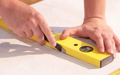 Hände schneiden präzise eine Tapete entlang einer Wasserwage