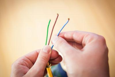 Hände, die ein Kabel bearbeiten.