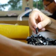 Hände suchen ein Elektrostecker aus einem Haufen Teile heraus